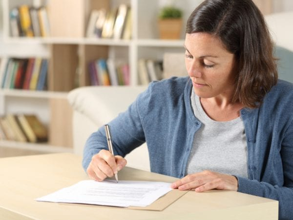 Serious adult woman signing a document
